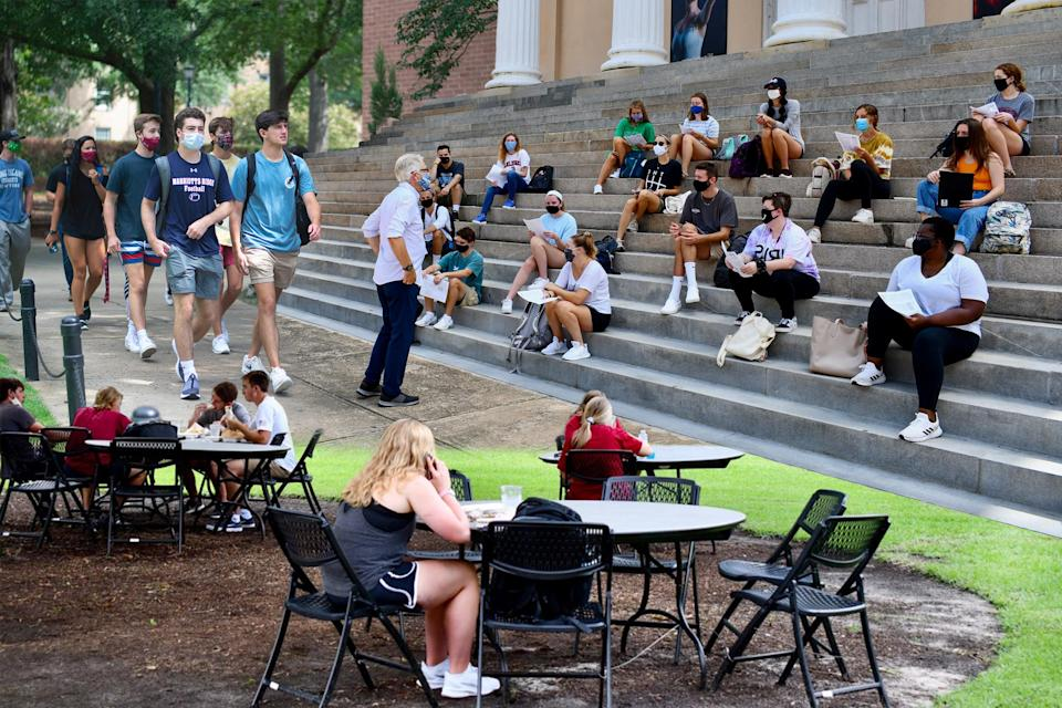 From top left: Students walking around Russell House, University of South Carolina's student union; A professor holds class outside on the steps of Longstreet Theatre on USC's campus; USC put tables and chairs on the grass around the student union so there is more seating area because indoor capacity is limited. Students are expected to wipe down these tables and chairs themselves upon use