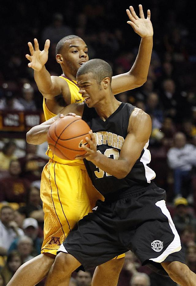 Wofford guard Spencer Collins, right, tries to push through the defense of Minnesota guard Andre Hollins in the first half of an NCAA college basketball game Thursday, Nov. 21, 2013, in Minneapolis. (AP Photo/Stacy Bengs)