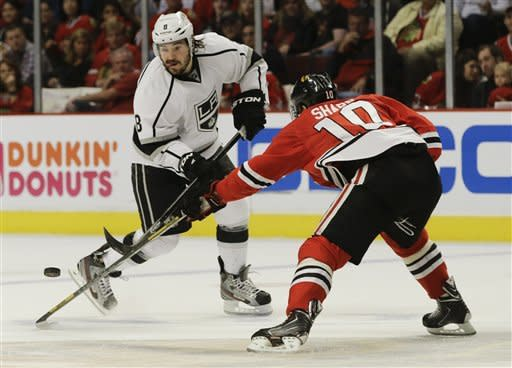Los Angeles Kings defenseman Drew Doughty (8) battles for the puck against Chicago Blackhawks center Patrick Sharp (10) during the first period of Game 2 of the NHL hockey Stanley Cup Western Conference finals, Sunday, June 2, 2013, in Chicago. (AP Photo/Nam Y. Huh)