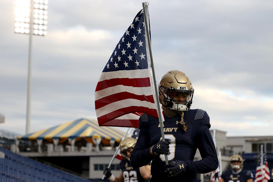 ANNAPOLIS, MARYLAND - DECEMBER 05: Cameron Kinley #3 of the Navy Midshipmen carries an American flag as the team takes the field against the Tulsa Golden Hurricane at Navy-Marine Corps Memorial Stadium on December 05, 2020 in Annapolis, Maryland. (Photo by Rob Carr/Getty Images)