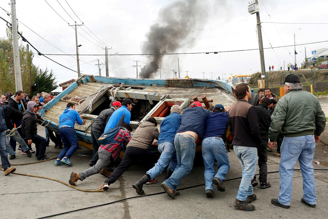 Fishermen block a road with a boat during a protest calling on the government to help ease the economic effects of an harmful algal bloom that had affected their livelihoods at Ancud on Chiloe island in Chile, May 5, 2016. REUTERS/Pablo Sanhueza EDITORIAL USE ONLY. NO RESALES. NO ARCHIVE