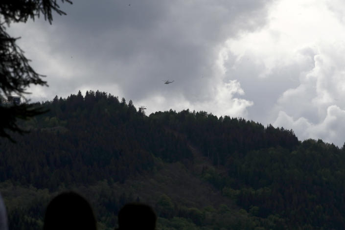 An helicopter flies over the cable car line that collapsed, near Stresa, Italy, Sunday, May 23, 2021. A cable car taking visitors to a mountaintop view of some of northern Italy's most picturesque lakes plummeted to the ground Sunday and then tumbled down the slope, killing at least 13 people and sending two children to the hospital, authorities said. (AP Photo/Antonio Calanni)