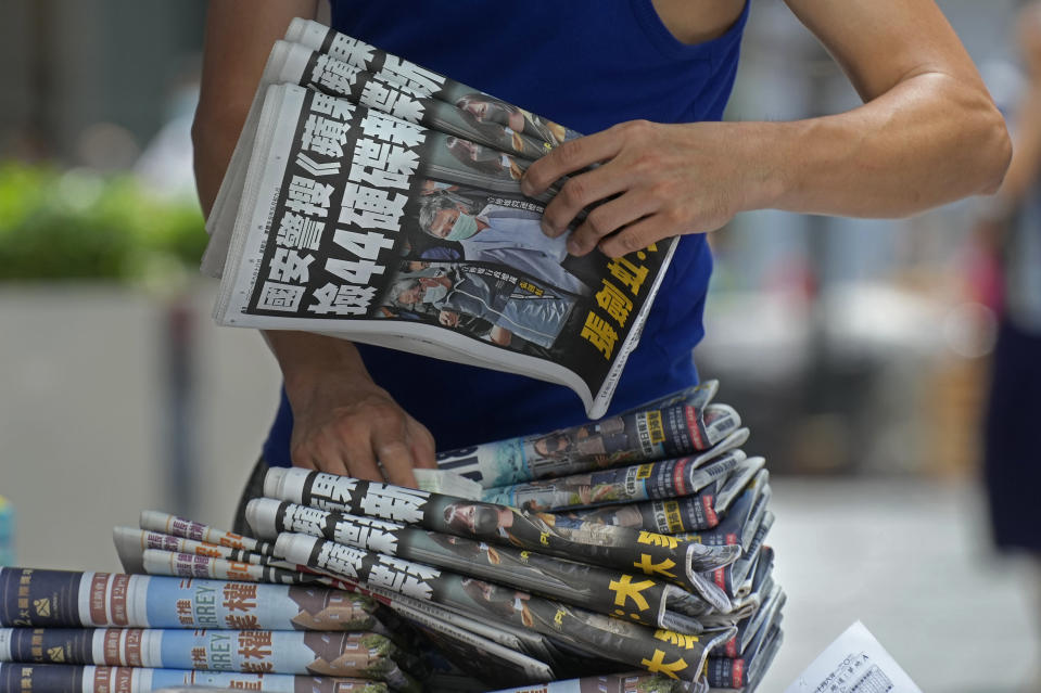 A vendor adjusts copies of Apple Daily at a news stand in downtown Hong Kong Friday, June 18, 2021. The pro-democracy paper increased its print run to 500,000 copies on Friday, a day after police arrested five top editors and executives and froze $2.3 million in assets linked to the media company. (AP Photo/Vincent Yu)