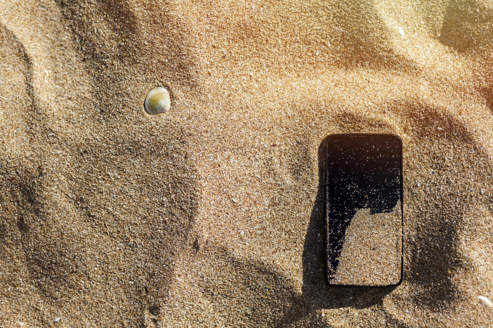 Mobile phone fallen and lost in the sand