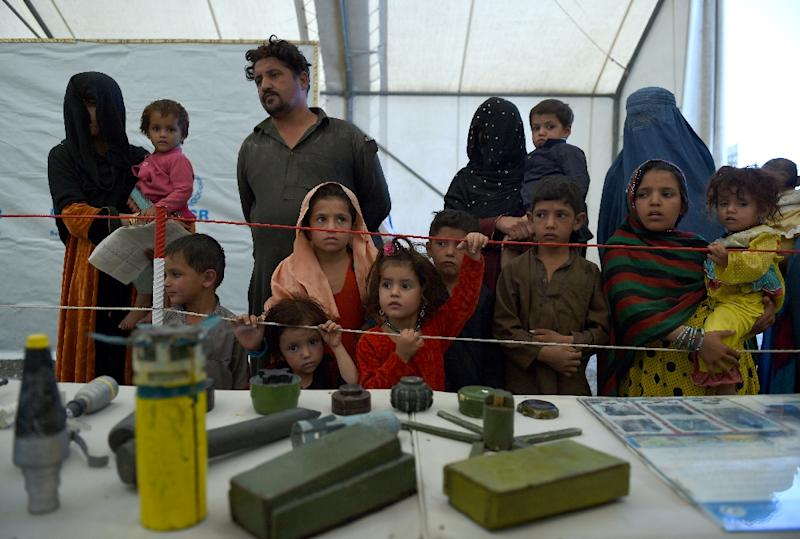 Afghan refugee families look at samples of bombs and mines at the United Nations High Commissioner for Refugees (UNHCR) camp on the outskirts of Kabul on September 27, 2016 (AFP Photo/Wakil Kohsar)