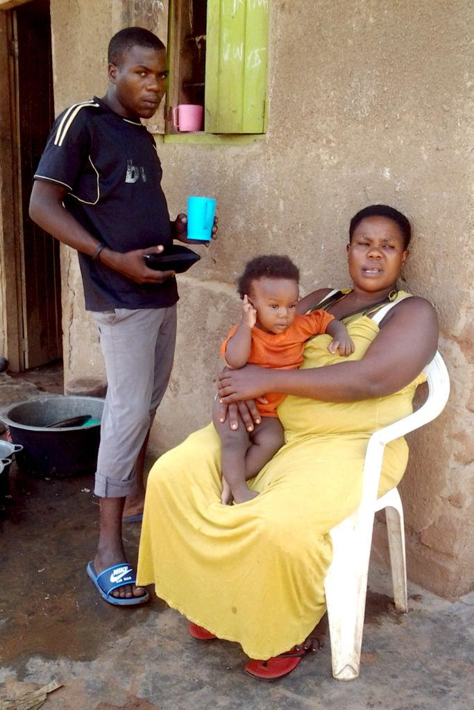 The Ugandan woman Mariam Nabatanzi sits in front of the house with her 20-year-old son Akim and youngest child, Sudaisha.