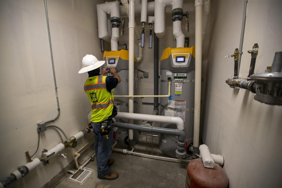 Everett Reid, assistant superintendent, views high-efficiency natural gas boilers at Day Creek Villas.