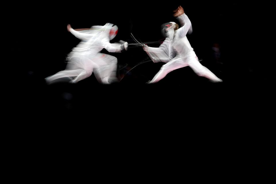 <p>Japan's Sera Azuma (R) compete against Canada's Kelleigh Ryan in the women's foil individual qualifying bout during the Tokyo 2020 Olympic Games at the Makuhari Messe Hall in Chiba City, Chiba Prefecture, Japan, on July 25, 2021. (Photo by Fabrice COFFRINI / AFP)</p>
