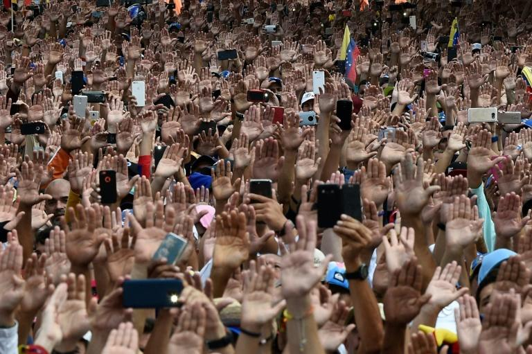 People raise their hands during a mass opposition rally against President Nicolas Maduro on January 23, 2019, after National Assembly head Juan Guaido declared himself the country's 'acting president'