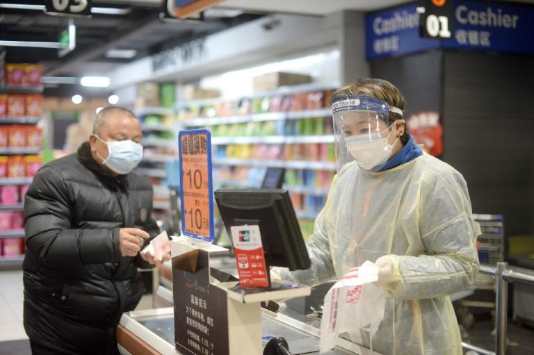 A staff member wearing a protective mask and suit works at a supermarket in Wuhan, the epicentre of the novel coronavirus outbreak