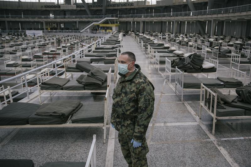 A Serbian military personnel wearing a protective mask stands amongst beds set up inside Belgrade's Spens Hall. Source: AFP via Getty Images