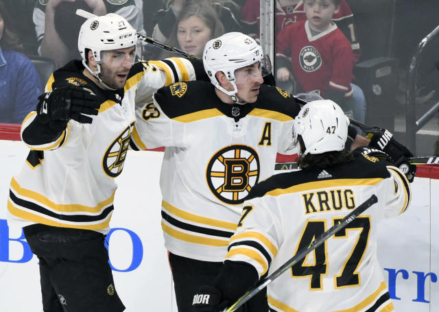 Boston Bruins' Patrice Bergeron (37), Brad Marchand (63) and Torey Krug (47) celebrate a goal by Marchand against the Minnesota Wild during the overtime period of an NHL hockey game Sunday, March 25, 2018, in St. Paul, Minn. The Bruins won 2-1 in overtime. (AP Photo/Hannah Foslien)