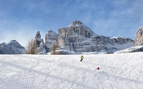 People skiing on a piste in Corvara with a backdrop of the Dolomites - Credit: Alex Filz
