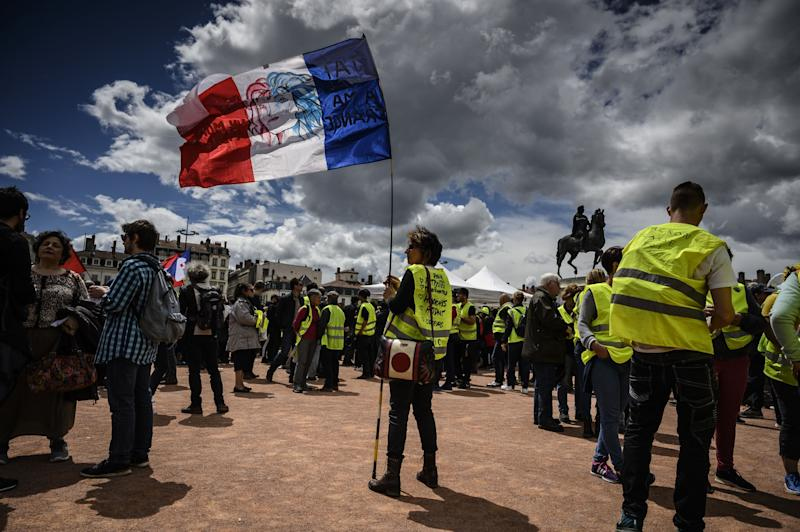 "A protestor holds a French flag at Bellecourt square in Lyon, central-eastern France, during an anti-government demonstration called by the ""Yellow Vest"" (Gilets Jaunes) movement, on May 11, 2019. (Photo by JEAN-PHILIPPE KSIAZEK / AFP) (Photo credit should read JEAN-PHILIPPE KSIAZEK/AFP/Getty Images)"
