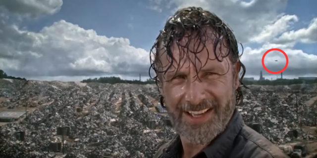 Rick overlooking wasteland, unexplained flying object in the background