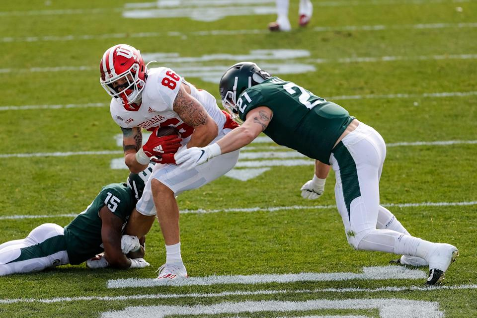 Michigan State cornerback Angelo Grose, left, and linebacker Cal Haladay tackle Indiana tight end Peyton Hendershot during the first half at Spartan Stadium in East Lansing, Saturday, Nov. 14, 2020.
