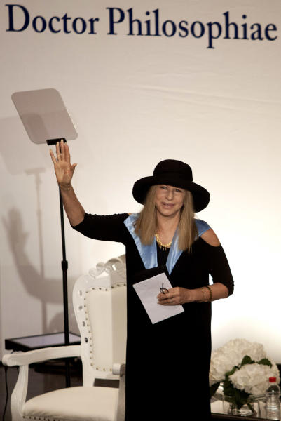 Entertainment star Barbra Streisand waves during a ceremony at the Hebrew University after she received an honorary doctorate in Jerusalem, Monday, June 17, 2013. Streisand waded into one of Israel's touchiest issues Monday on the first major stop of her tour of the country Jewish religious practices that separate men and women. (AP Photo/Dan Balilty)