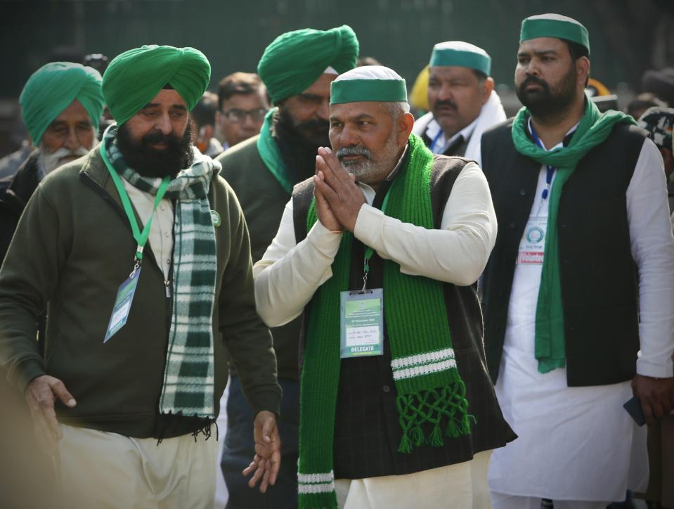 Farmer leader Rakesh Tikait, center, greets the crowd before going in for a meeting with government representatives in New Delhi. (AP Photo/Manish Swarup)