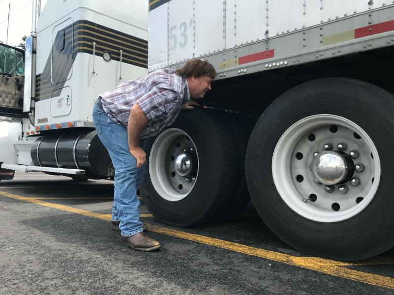 In this June 13, 2019 photo, truck driver Terry Button looks over his trailer during at stop in Opal, Va. The Trump administration has moved a step closer to relaxing federal regulations governing the amount of time truck drivers can spend behind the wheel.  (AP Photo/Tom Sampson)
