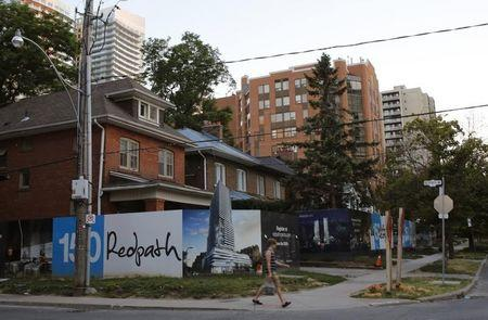 Billboards surround a row of houses set to be demolished to make way for a condominium development feeding the real estate market ofToronto
