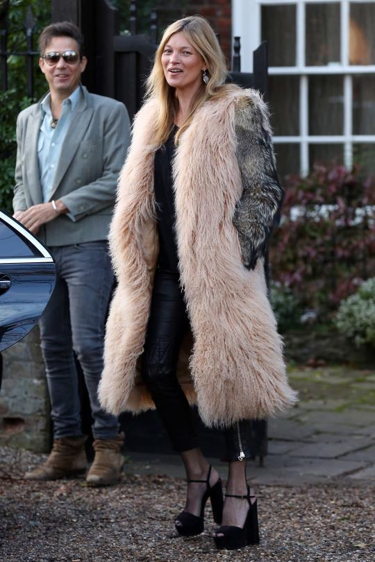 <p>Moss layered her leather cigarette pants over black fishnets and topped off the look with a glamorous two-toned fur coat, and platform heels.</p>