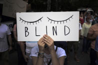 "A protester holds a poster in front of the German Embassy in Sofia, Bulgaria, Wednesday, Aug. 12, 2020. Several hundred anti-government protesters gathered in front of Germany's embassy in Sofia, calling on Berlin and Brussels to ""open their eyes"" to widespread corruption in Bulgaria. During the peaceful protest, dubbed ""Eyes Wide Shut,"" organizers complained that the European Union has willfully ignored the state of affairs in its poorest member state. (AP Photo/Valentina Petrova)"