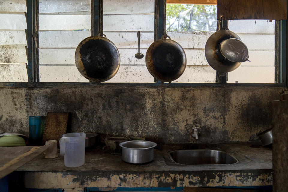 Pots and pans hang in the kitchen of workers' living quarters in a palm oil plantation run by the government-owned Felda in Malaysia in early 2020. Jum, a former worker who escaped from this same plantation, said the company confiscated, and later lost his Indonesian passport, leaving him vulnerable to arrest and forcing him to hide in the jungle. (AP Photo/Ore Huiying)