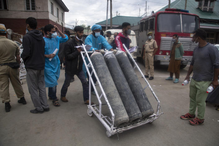 Local men hired by administration assist transport of oxygen cylinders in the premises of a hospital in Srinagar, Indian controlled Kashmir, Sunday, May 23, 2021. (AP Photo/Mukhtar Khan)