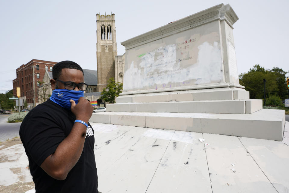 Devon Henry, owner of Henry Enterprises, adjusts his mask in front of the pedestal that used to hold the statue of Confederate General J.E.B Stuart during an interview Tuesday Sept. 15, 2020, in Richmond, Va. Henry is a Black businessman whose construction company took on a job the city says others were unwilling to do. (AP Photo/Steve Helber)