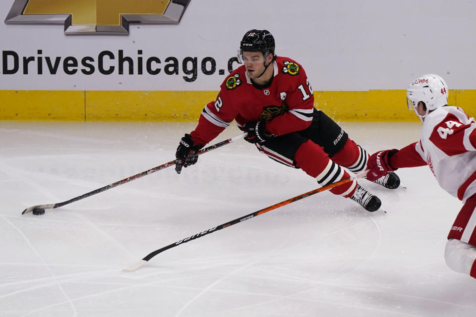 Chicago Blackhawks left wing Alex DeBrincat, left, looks to pass against Detroit Red Wings defenseman Christian Djoos during the second period of an NHL hockey game in Chicago, Saturday, Feb. 27, 2021. (AP Photo/Nam Y. Huh)