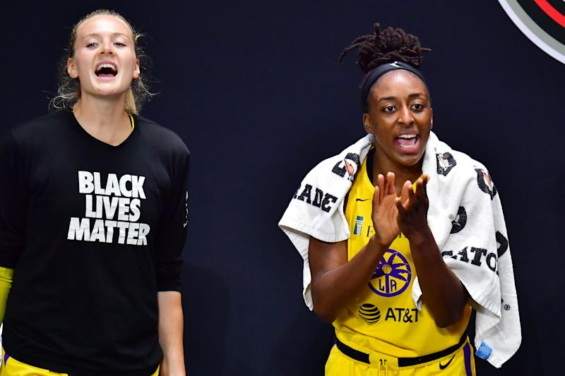 Marie Gulich to the left in a black Black Lives Matter shirt. Nneka Ogwumike in a jersey, clapping on the bench.