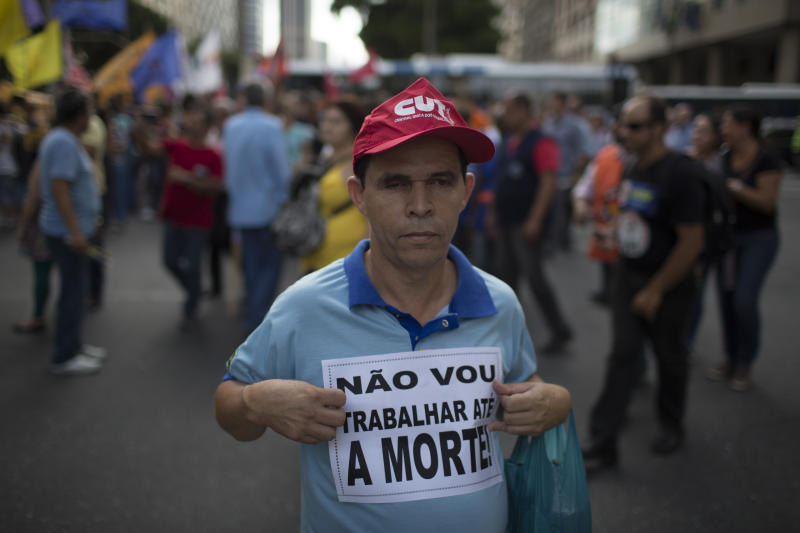 "A demonstrator holds a sign that reads in Portuguese ""I will not work until I die"" during a protest against federal government proposed reforms in Rio de Janeiro, Brazil, Wednesday, March 15, 2017. People protested across the country against proposed changes to work rules and pensions. (AP Photo/Leo Correa)"