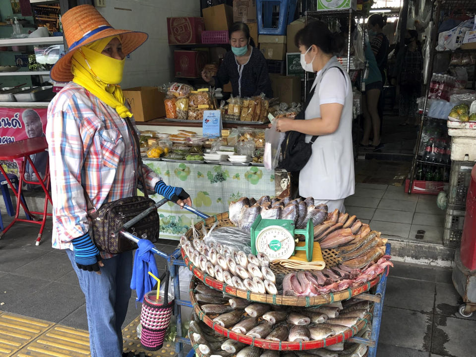A vendor wearing a face covering to help prevent the spread of coronavirus sells fish from a pushcart outside a produce market in central Bangkok on Wednesday, Dec. 23, 2020. Thailand has kept the coronavirus largely in check for most of the year but is facing a challenge from a large outbreak of the virus among migrant workers linked to a major seafood market close to the Thai capital.(AP Photo/Adam Schreck)