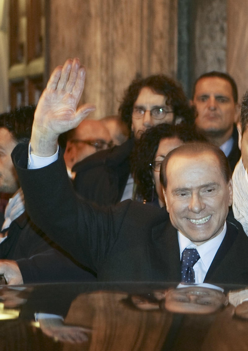 Italian Premier Silvio Berlusconi waives as he leaves at the end of a meeting with his allies in the Italian Senate in Rome, Thursday, Nov. 10, 2011.  Arriving earlier at the Senate, where the budget committee approved the reforms Thursday evening, Berlusconi was heckled by some 20 bystanders. The prospect of an Italian government led by leading economist Mario Monti, after Berlusconi pledged to resign soon,  helped calm market jitters Thursday that the country was heading for a Greek-style economic crisis that would threaten the very existence of the euro currency itself.  (AP Photo/Riccardo De Luca)