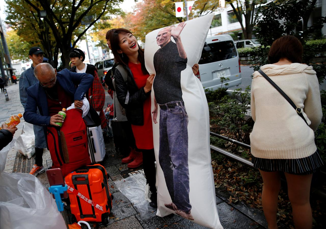 Ayano Tominaga poses with a cushion printed with a portrait of Apple co-founder Steve Jobs on it, as she waits in queue for the release of Apple's new iPhone X in front of the Apple Store in Tokyo's Omotesando shopping district, Japan, November 3, 2017.  REUTERS/Toru Hanai