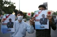 Supporters of presidential candidate Abdolnaser Hemmati hold posters of him in a street in Tehran