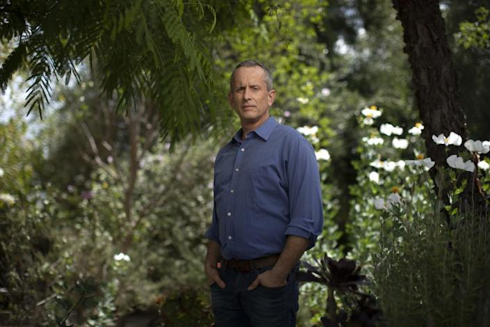 Michael Taylor Gray poses for a photo in front of a background of trees and flowers.