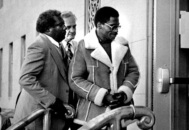 """FILE - In this Nov. 8, 1985 file photo, Rubin """"Hurricane"""" Carter, right, the former middleweight boxer, is escorted into federal court in Newark, N.J. Carter, who spent almost 20 years in jail after twice being convicted of a triple murder he denied committing, died at his home in Toronto, Sunday, April 20, 2014, according to long-time friend and co-accused John Artis. He was 76. (AP Photo/File)"""