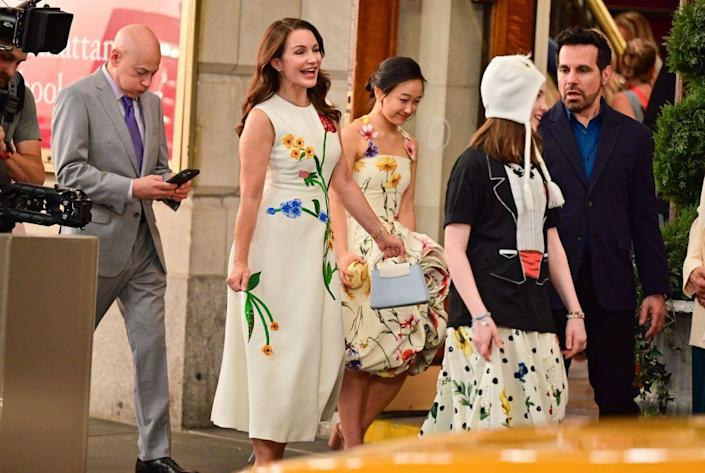 <p>The now grown-up Goldenblatt daughters, Parker Fong's Lily and Liliana Pizzuto's Rose, were spotted alongside set parents Evan Handler and Kristin Davis at the Lyceum Theatre near the Manhattan School of Music throughout filming wearing gorgeous Oscar de la Renta designs, Fong in the brand's altered floral-appliqué halter-neck dress and Pizzuto in its pleated printed cotton-blend poplin dress. Fong additionally opted for Loeffler Randall's Camellia bow heel sandals featuring an ankle strap pearl, while Pizzuto dressed down the look in a vintage tuxedo T-shirt and high-top sneakers by Comme des Garçons x Converse. </p>