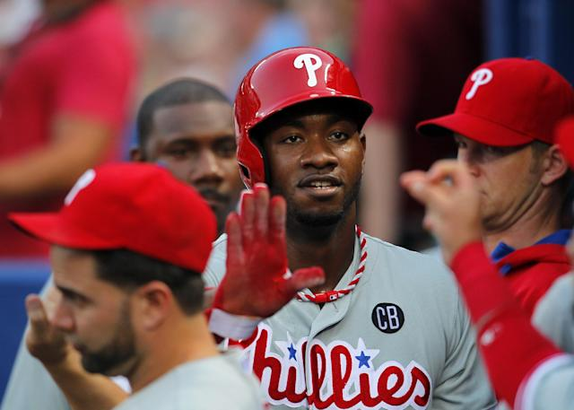 Philadelphia Phillies left fielder Domonic Brown (9) celebrates with teammates after scoring on a wild pitch in the fourth inning of a baseball game Tuesday, June 17, 2014, in Atlanta. (AP Photo/Todd Kirkland)