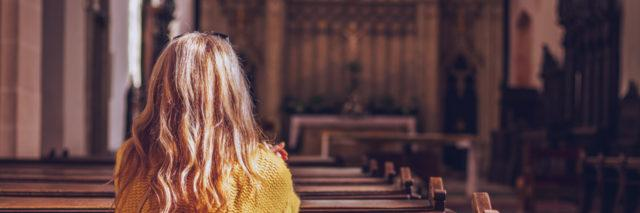 Woman in yellow sweater and blonde hair sitting in a pew at church praying