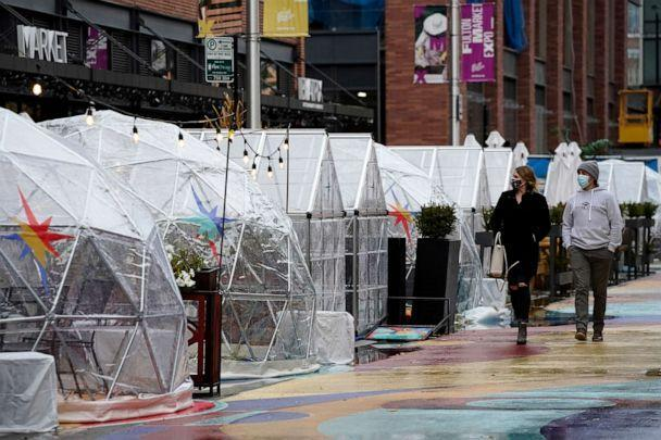 PHOTO: People walk by outdoor plastic dining bubbles on Fulton Market in Chicago, Oct. 18, 2020. (Nam Y. Huh/AP, FILE)