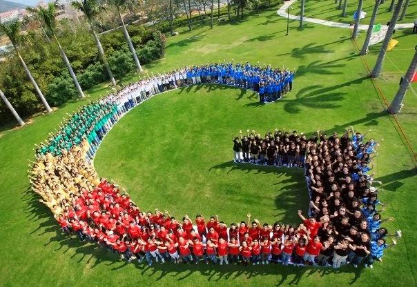 People wearing various colored shirts standing in the shape of a G on a grassy lawn