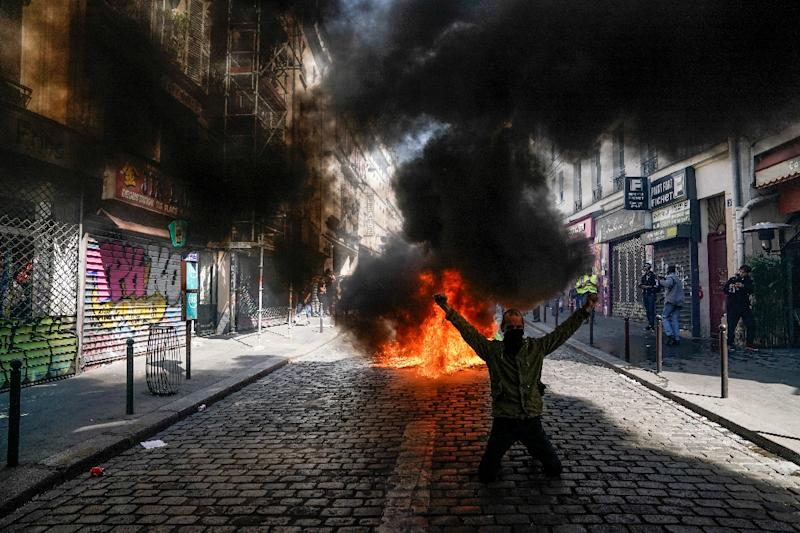 A protester in front of a fire during an anti-government demonstration in Paris (AFP Photo/Lionel BONAVENTURE)