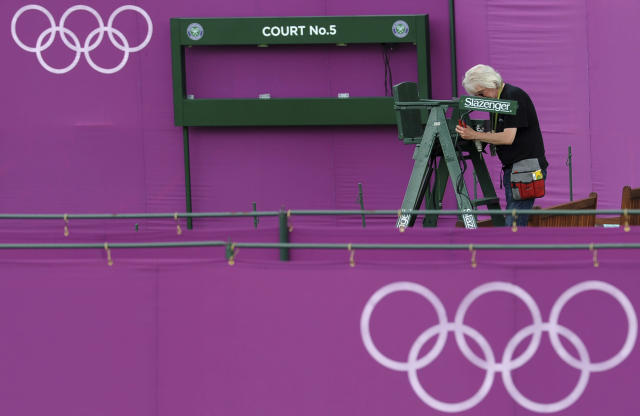 A workman helps erect Olympic hoarding on Court Five at the All England Lawn Tennis Club (AELTC) as preparations are made for the London 2012 Olympic Games, in London July 9, 2012. REUTERS/Ki Price (BRITAIN - Tags: SPORT OLYMPICS TENNIS)