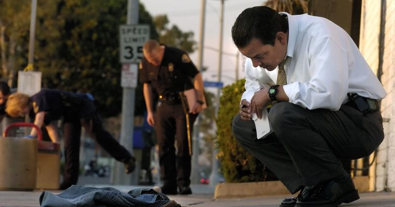 Long Beach police homicide detective examines the clothes of a teenager who was shot and killed.