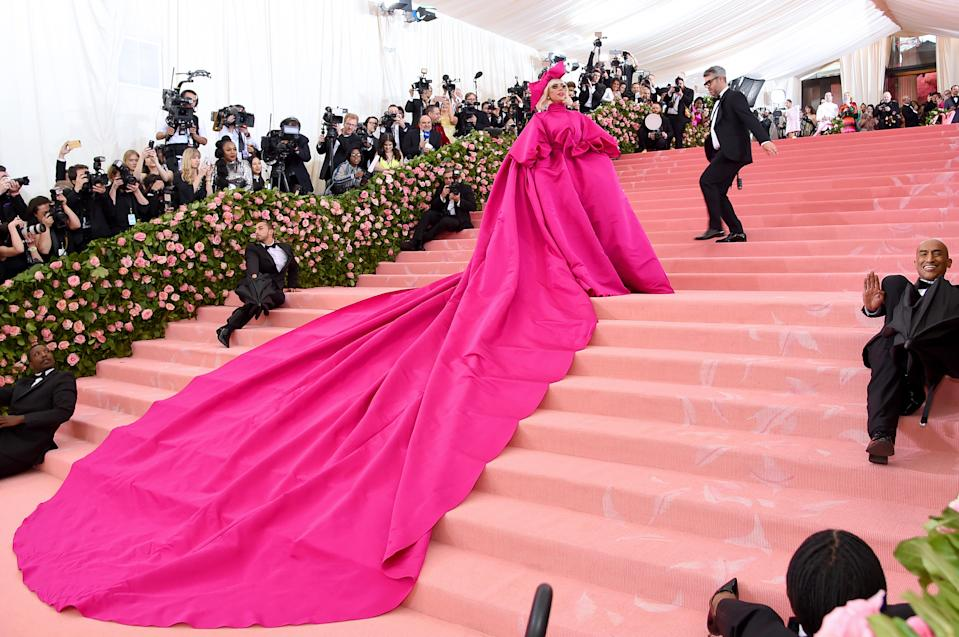The singer-turned-actress's 25-foot train was carried into the Met Gala by a group of suit-clad dancers [Photo: Getty]
