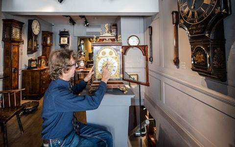 Antique clock seller Howard Walwyn goes through his shop in Kensington, London, changing the time on all the clocks - Credit: John Nguyen/JNVisuals