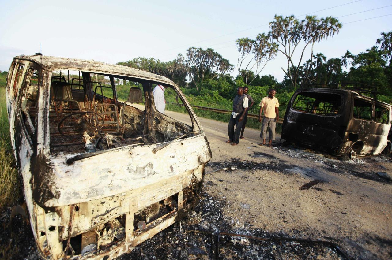 Wreckages of burnt cars are seen along the main road to Lamu from Mpeketoni after unidentified gunmen attacked the coastal Kenyan town of Mpeketoni, June 16, 2014. At least 48 people were killed and others wounded when more than two dozen unidentified gunmen attacked a coastal Kenyan town overnight, police and the Kenya Red Cross said on Monday. REUTERS/Joseph Okanga (KENYA - Tags: CIVIL UNREST CRIME LAW TPX IMAGES OF THE DAY)