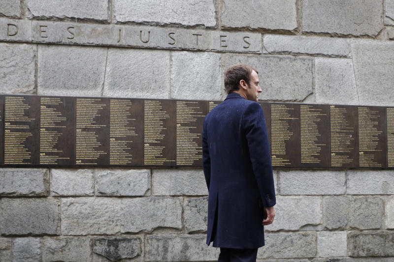 """FILE - In this Sunday, April 30, 2017 file picture, independent centrist presidential candidate Emmanuel Macron stands at the """"Mur des Justes"""" at the Shoah Museum, a wall on which 2,693 names of people who protected or saved Jews during World War II are engraved, in Paris,France. France's leading Jewish group is meeting with President Emmanuel Macron and is expected to ask him about a rise in anti-Jewish violence and protest the possible re-publication of anti-Semitic pamphlets by a renowned writer. (Philippe Wojazer/Pool Photo via AP, File)"""